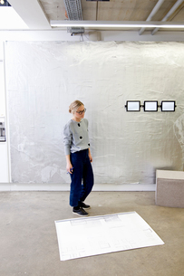 Architect in office looking at blueprintの写真素材 [FYI03560259]