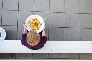 Overhead view of woman holding serving bowl of pastaの写真素材 [FYI03560311]