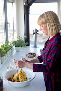 Woman stirring pasta in serving dishの写真素材 [FYI03560312]