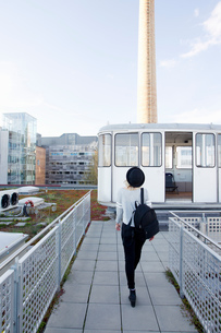Rear view of woman wearing hat carrying backpack on rooftop terraceの写真素材 [FYI03560322]