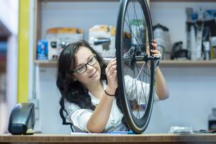 Woman in repair shop looking at bicycle wheelの写真素材 [FYI03560370]