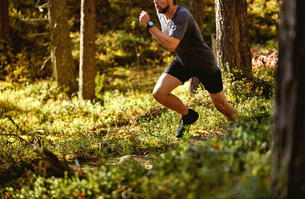Man running in forest, Keimiotunturi, Lapland, Finlandの写真素材 [FYI03560564]