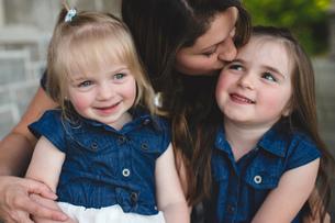 Girls sitting on mothers lap smilingの写真素材 [FYI03560635]