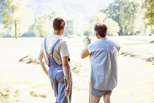 Rear view of two male farmworkers discussing harvestの写真素材 [FYI03560719]