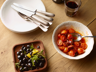 Overhead view of table with bowl of black olives and bowl of Spanish tomatoes with chorizoの写真素材 [FYI03560759]