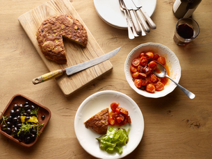 Overhead view of table with Spanish potato tortilla and bowl  tomatoes and chorizoの写真素材 [FYI03560760]