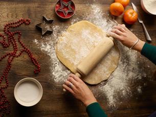 Overhead view of teenage girl's hands rolling christmas star biscuit doughの写真素材 [FYI03560766]