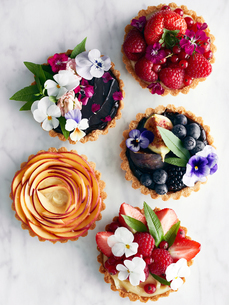 Display of variety of tart, fruit and flowersの写真素材 [FYI03560930]