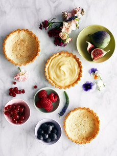 Display of variety of tart, fruit and flowersの写真素材 [FYI03560931]