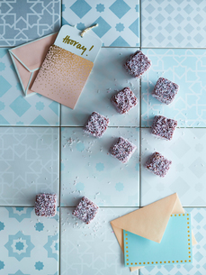 Cubes of sweets on tiles, next to greeting cardsの写真素材 [FYI03560952]