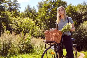 Portrait of young woman on bicycle gazing from rural dirt trackの写真素材 [FYI03560976]