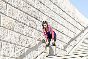 Young female runner taking a break on urban stairwayの写真素材 [FYI03561032]