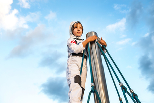 Boy in astronaut costume looking out from top of climbing frameの写真素材 [FYI03561036]