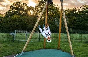Portrait of boy in astronaut costume riding upside down on playground zip wireの写真素材 [FYI03561045]