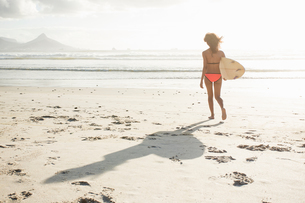 Young female surfer on sunlit beach, Cape Town, Western Cape, South Africaの写真素材 [FYI03561057]