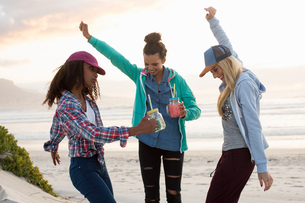 Three young female friends dancing together on beach, Cape Town, Western Cape, South Africaの写真素材 [FYI03561070]