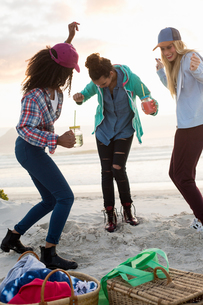 Three young female friends dancing at beach picnic, Cape Town, Western Cape, South Africaの写真素材 [FYI03561071]