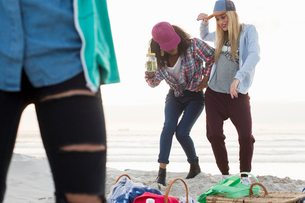Three young female friends fooling around at beach picnic, Cape Town, Western Cape, South Africaの写真素材 [FYI03561072]