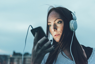 Young freckled woman listening to headphones looking at smartphone at duskの写真素材 [FYI03561103]