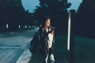 Young woman reading smartphone texts in park at nightの写真素材 [FYI03561105]