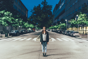 Portrait of young woman standing in centre of city road at nightの写真素材 [FYI03561111]