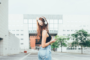 Young woman listening to headphones with hand on head outside office buildingの写真素材 [FYI03561126]