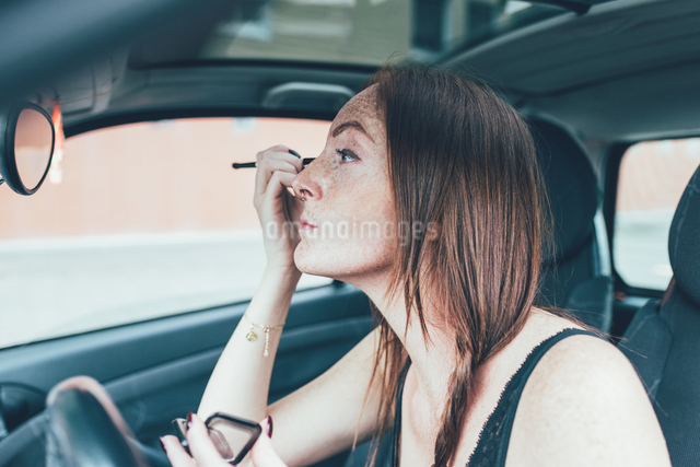 Young woman with freckles applying eyeshadow in car mirrorの写真素材 [FYI03561139]