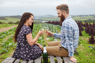 Couple in rural location sitting on pallets making a toastの写真素材 [FYI03561256]