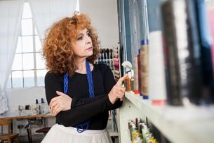 Woman in sewing workshop looking awayの写真素材 [FYI03561349]