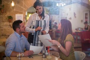 Waitress serving customers in restaurantの写真素材 [FYI03561363]