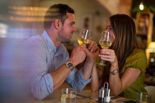 Couple toasting wine in restaurantの写真素材 [FYI03561366]