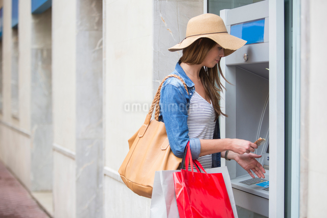 Woman withdrawing cash from cash machineの写真素材 [FYI03561381]