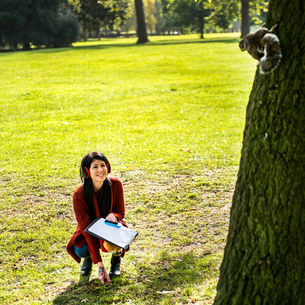 Young woman crouching in park, looking at squirrel in treeの写真素材 [FYI03561419]