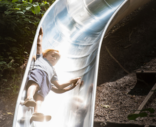Boy sliding down playground slideの写真素材 [FYI03561474]