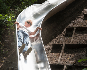 Woman sliding down playground slideの写真素材 [FYI03561475]