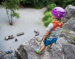 Boy wearing climbing helmet standing on top of rock looking downの写真素材 [FYI03561528]