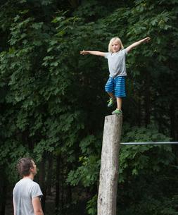 Boy on one leg, arms open, balancing on poleの写真素材 [FYI03561535]