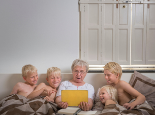 Grandmother in bed with grandsons using digital tabletの写真素材 [FYI03561544]