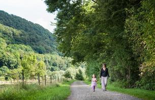 Mother and daughter walking on rural road, Porta Westfalica, North Rhine Westphalia, Germanyの写真素材 [FYI03561569]