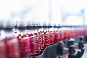 Bottles filled with flavoured water on production line in spring water factoryの写真素材 [FYI03561582]