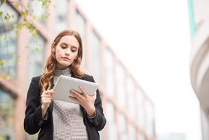 Businesswoman in city using digital tabletの写真素材 [FYI03561649]