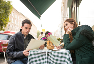 Couple at pavement cafe looking at menu smilingの写真素材 [FYI03561676]