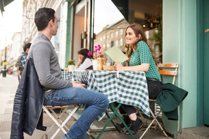 Couple at pavement cafe looking at menu smilingの写真素材 [FYI03561678]
