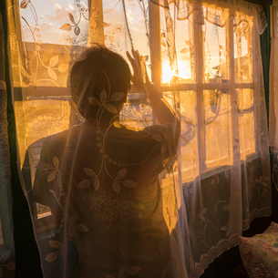 Mid adult man, behind net curtain, looking out of window at sunset, rear viewの写真素材 [FYI03561777]
