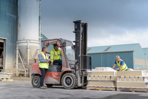 Manager talking to forklift truck driver outside architectural stone factoryの写真素材 [FYI03561784]