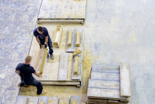Overhead view of workers moulding stone in architectural stone factoryの写真素材 [FYI03561798]