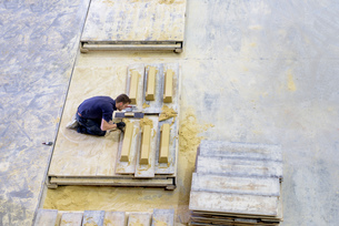 Overhead view of worker moulding stone in architectural stone factoryの写真素材 [FYI03561799]