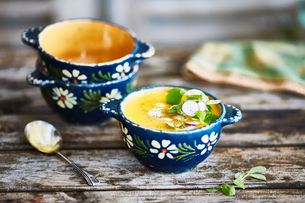 Bowl of garnished soup on wooden tableの写真素材 [FYI03561811]