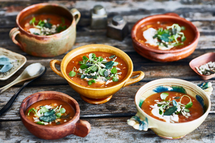Bowls of garnished soup on wooden tableの写真素材 [FYI03561815]