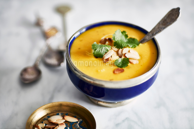 Bowl of butternut squash soup, garnished with toasted almonds and parsleyの写真素材 [FYI03561816]